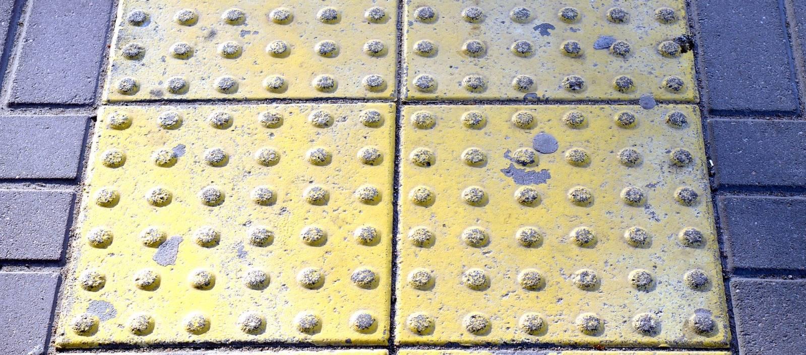 Señalización accesibilidad en la acera de la calle