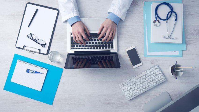 Mesa de un médico rodeado de herramientas tradicionales y tecnologícas